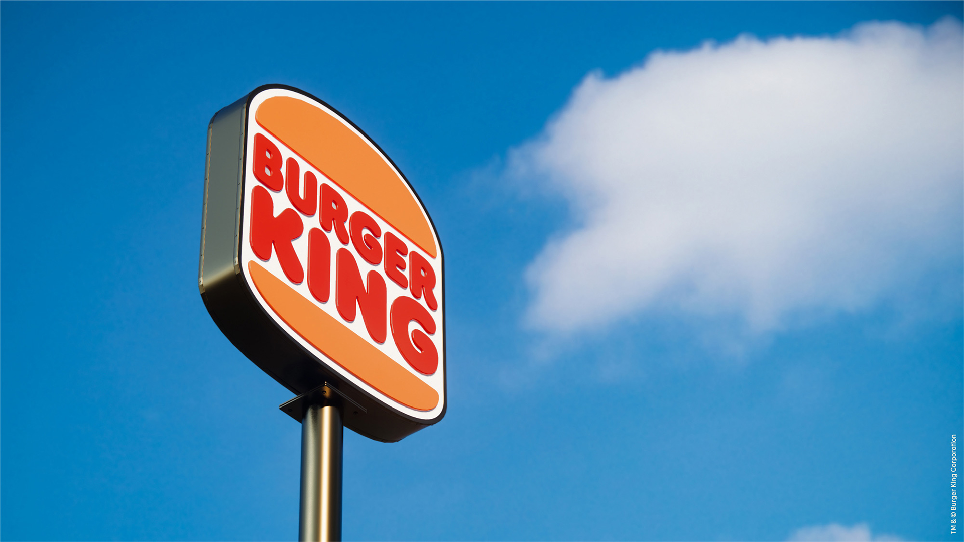 Large Burger King sign with blue sky behind it